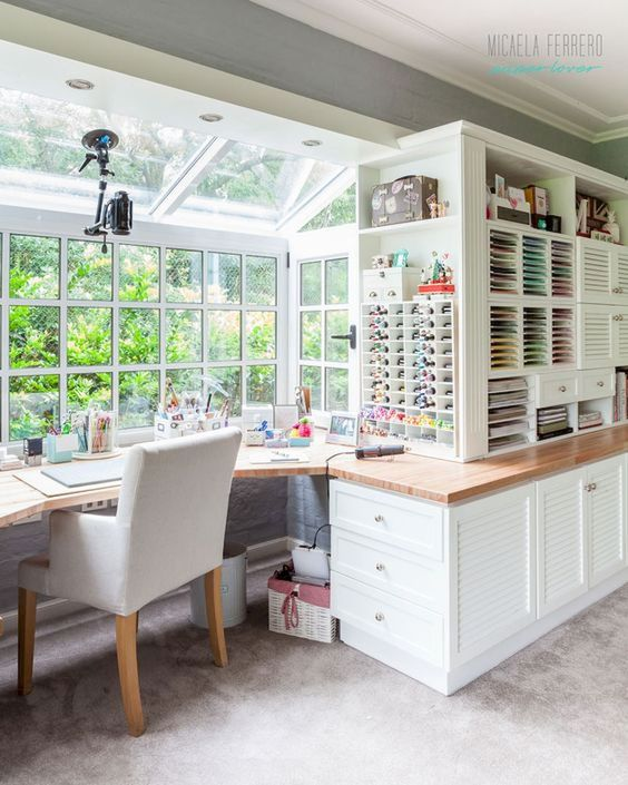study, rug, white bottom cabinet, white shelves, white framed glass window and ceiling, wooden floating table, white chair