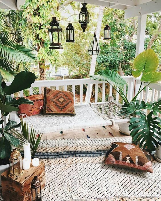 terrace, wooden floor, rug, white wooden bench with white woven seat, moroccan pendants, plants, wooden box