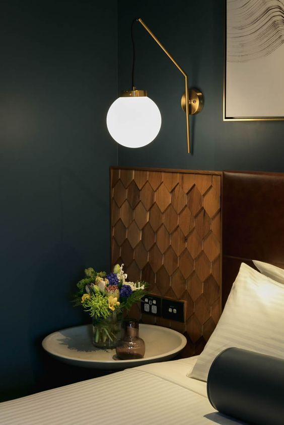 white ball sconce, dark green wall, wooden headboard, side table, white striped linen