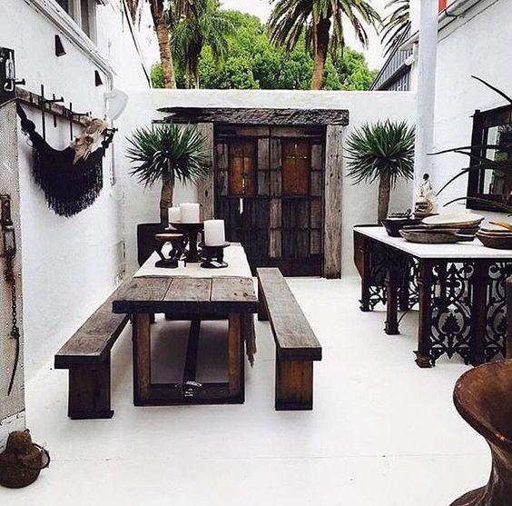 white patio, seamless floor, dark brown wooden dining set, dark wooden door