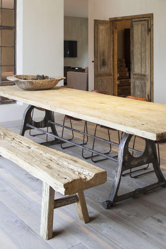 wooden dining table with metal legs, wooden bench, wooden floor, white wall, wooden door