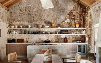 wooden table, thin metal legs, wooden chairs, woven cushion and back, wall stones, wooden ceiling, pale floor stones