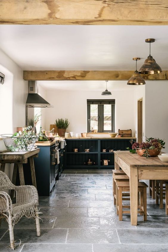 wooden table, wooden stools, grey floor tiles, white wall, dark blue wooden cabinet and shelves, wooden top, golden lamp, white rattan bench