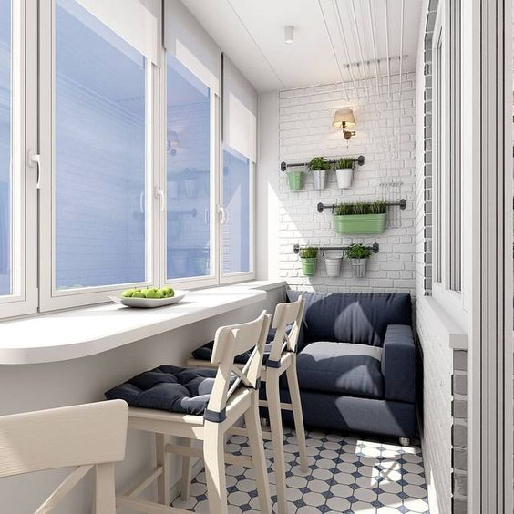 balcony, patterned floor tiles, exposed brick wall, grey sofa, white floating table, white wooden chairs with blue cushion