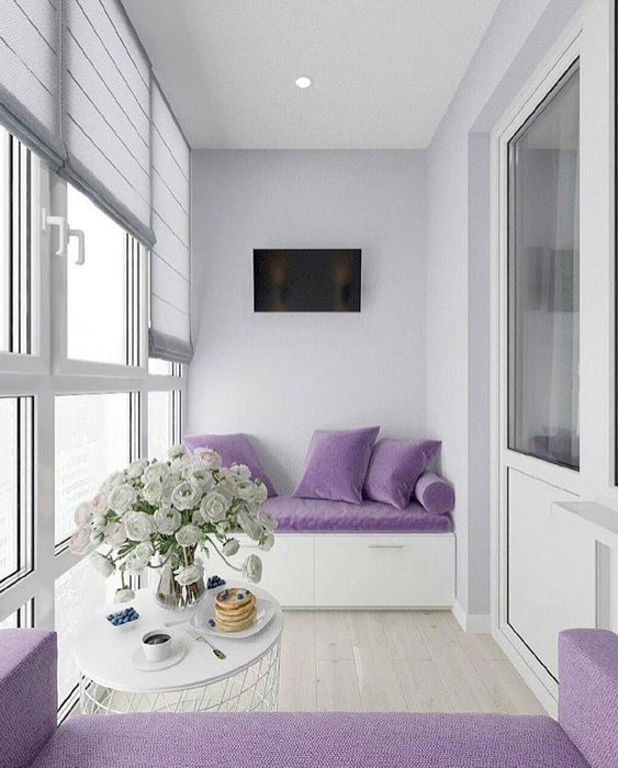 balcony, white wooden floor, white wall, white built in bench with purple cushion, purple pillows, white coffee table