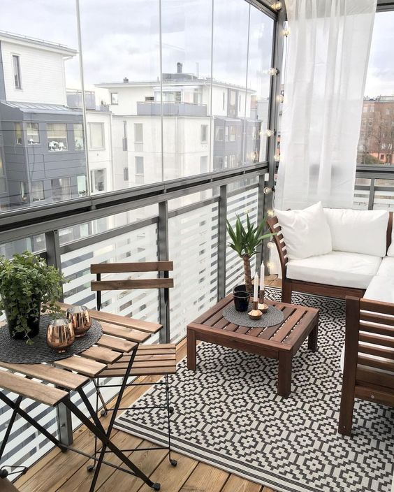 balcony, wooden floor, grey fence, see through screen, white curtain, wooden bench with white cushion, wooden coffee table, wooden chairs, wooden table