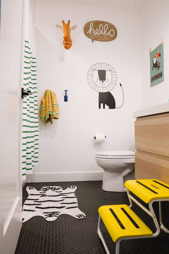 bathroom, black tiny hexagonal tiles, white wall, white toilet, wooden cabinet, white top, striped curtain, yellow stairs