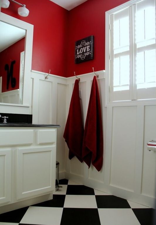 bathroom, black white checkered floor, white wainscoting, red wall, white framed window, white anity, white framed mirror