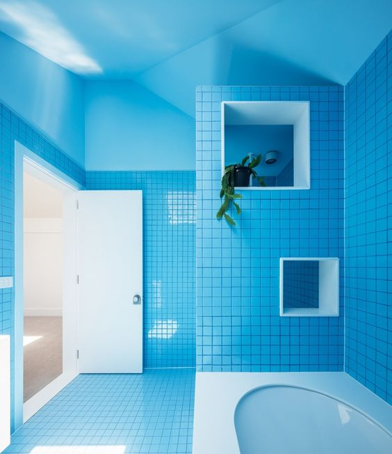 bathroom, blue square floor and wall tiles, white tub, blue wall, blue ceiling, white hole for plants, white door