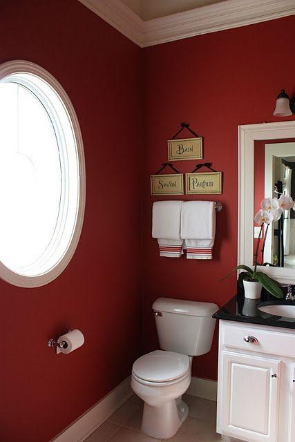 bathroom, grey floor, red wal, wite framed round window, white cabinet, white framed mirror, white sconce, white toilet