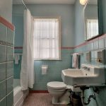 Bathroom, Orange Patterned Floor Tiles, Light Teal Wall Tiles And Wall, White Toilet, White Sink, White Tub, White Curtain
