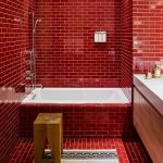 Bathroom, Red Smal Subway Tiles On Wall And Floor, Wooden Cabinet, White Sink, White Tub, White Rug