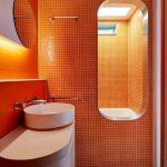 Bathroom, White Floor Tiles, Orange Wall Square Tiles, White Modern Vanity, White Round Sink, Mirror