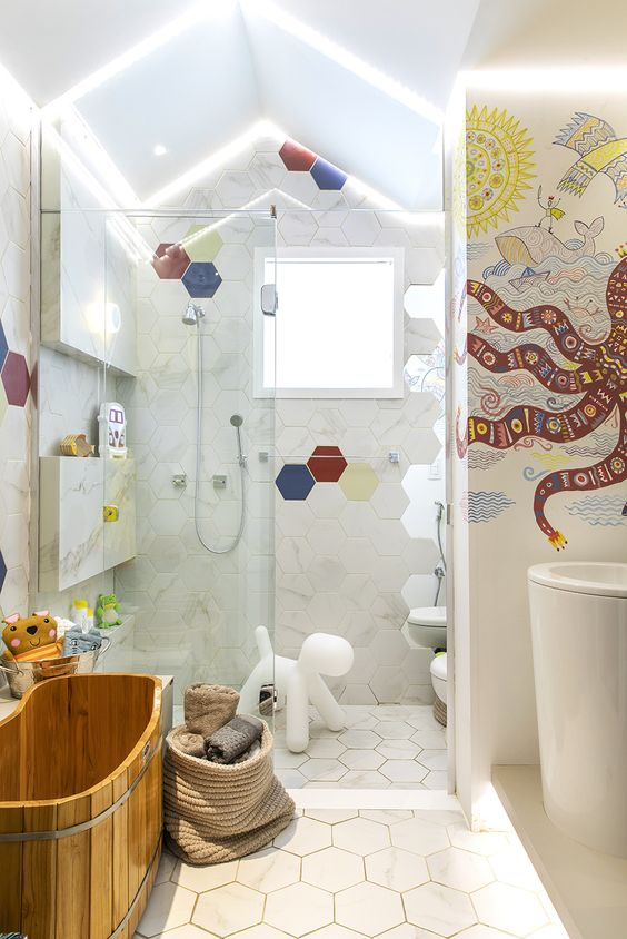 bathroom, white hexagonal floor tiles, white wall, LED lights on the ceiling, octopus sticker on the wall, wooden tub, white sink, white toilet
