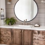 Bathroom, White Wall, Patterned Floor Tiles, Brown Accent Wall, Wooden Cabinet, White Top, Round Mirror, Bulb Sconces