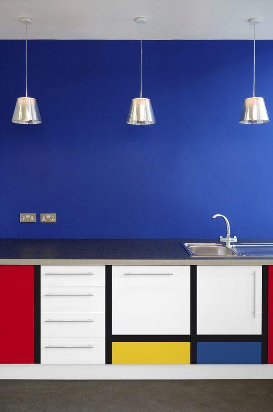 bedroom, grey floor, blue wall, cabinet with pop art, silver pendants, silver kitchen top