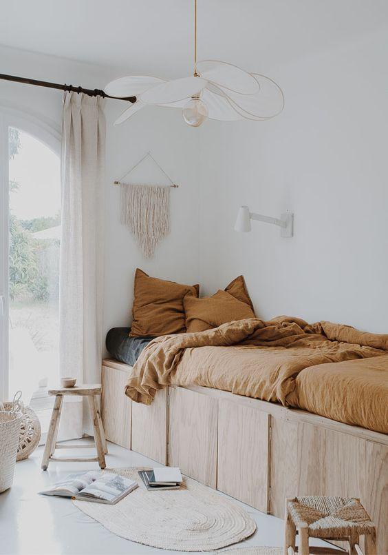 bedroom, white floor, plywood bed platform, white wall, white pendant, rug, rattan stools,