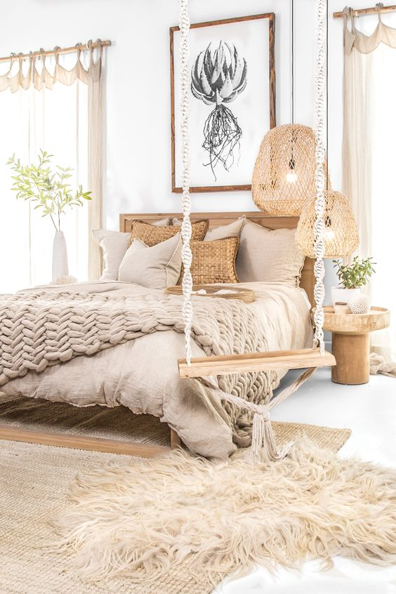 bedroom, white floor, rattan rug, brown linen, wooden bed platform, rattan pendant, wooden side table, white wall, wooden swing