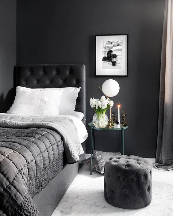 bedroom, white marble floor, black wall, black bed with tufted headboard, black tufted ottoman, side table