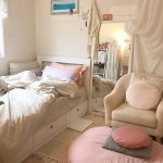 Bedroom, Wooden Floor, White Wall, White Bed Platform With Drawers, Beige Chairs, Pink Large Ottoman, Standing Mirror, Brown Rug