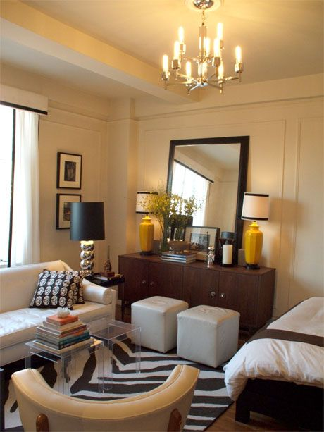 bedroom, wooden floor, white wall, white ceiling, chandelier, black bed platform, white sofa, white square ottomans, wooden cabinet, acrylic table