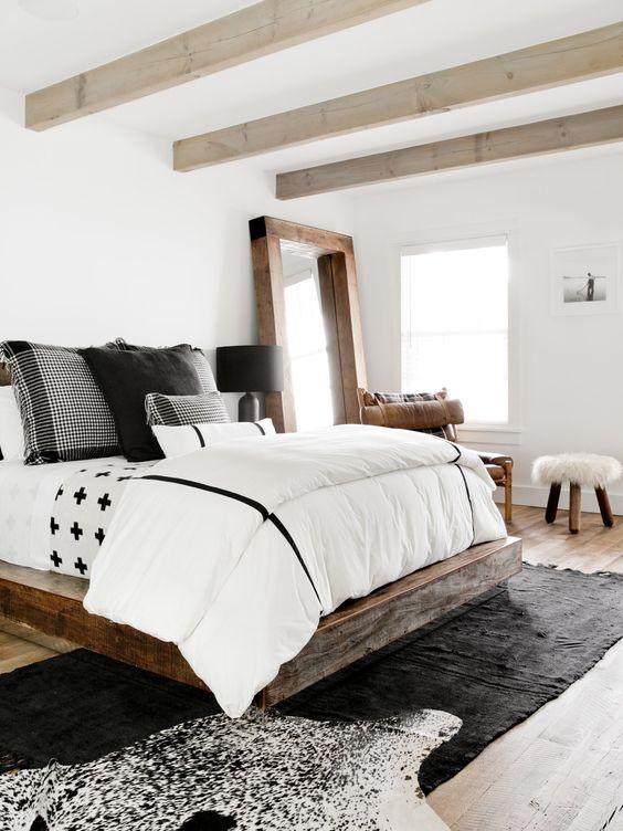 bedroom, wooden floor, wooden bed frame, white wall, wooden framed mirror, white bed, wooden chairs, wooden stool, black rug, wooden beams on the ceiling