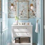 Bird Wallpaper Corner, Blue Wainscoting Wall, White Wooden Vanity, White Floor Tiles, Golden Framed Mirror, Sconces