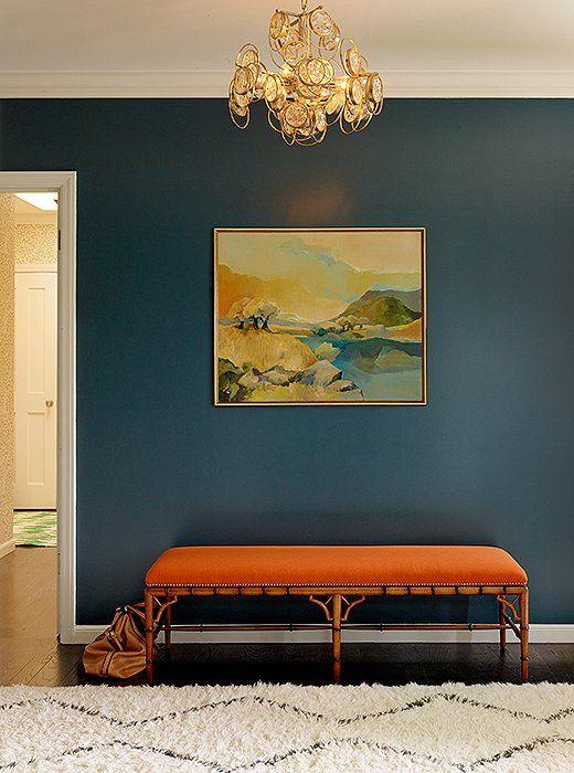bright entrance, blue wall, orange bench, golden chandelier