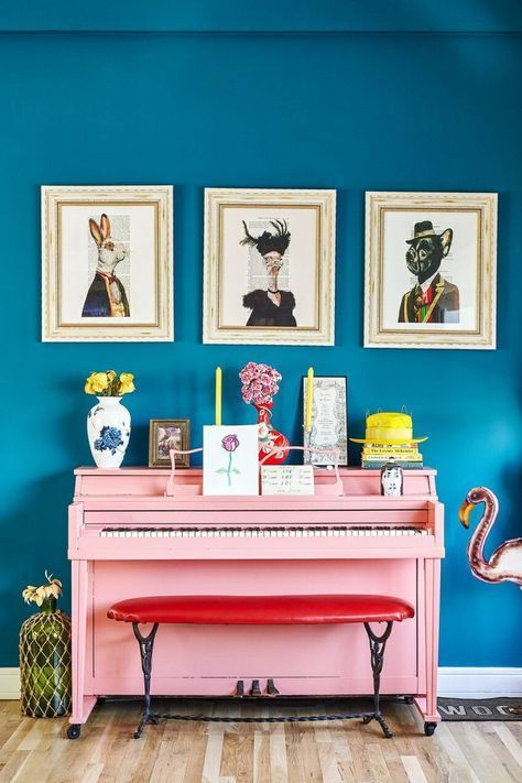 bright entrance, blue wall, pink piano, wooden floor, red bench