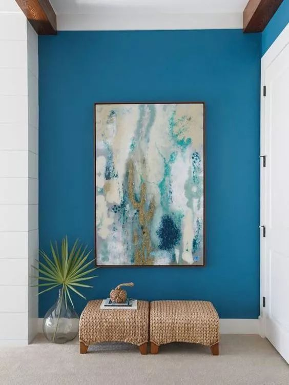 bright entrance, blue wall, white grey floor, rattan ottoman