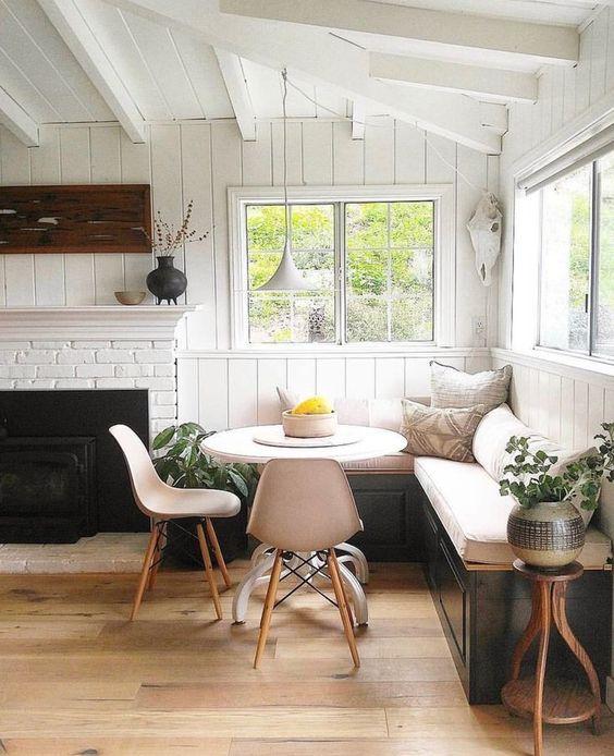 dining corner, black wooden bench, white cushion, white wooden plank wall, white wooden beams, white round table, cream modern chair, black fireplace