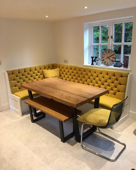 dining nook, cream floor, white bench, yellow tufted cushion, wooden table, wooden bench, metal chair, yellow cushion