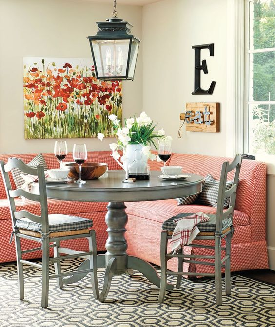 dining nook, wooden floor, patterned rug, pink corner sofa, grey round table, grey wooden chairs, pendant
