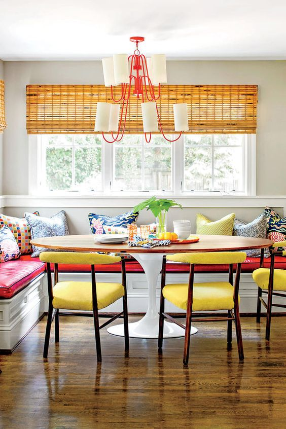 dining nook, wooden floor, white built in corner bench with red cushion, white wall, yellow bamboo curtain, round wooden table, yellow chairs, white red chandelier