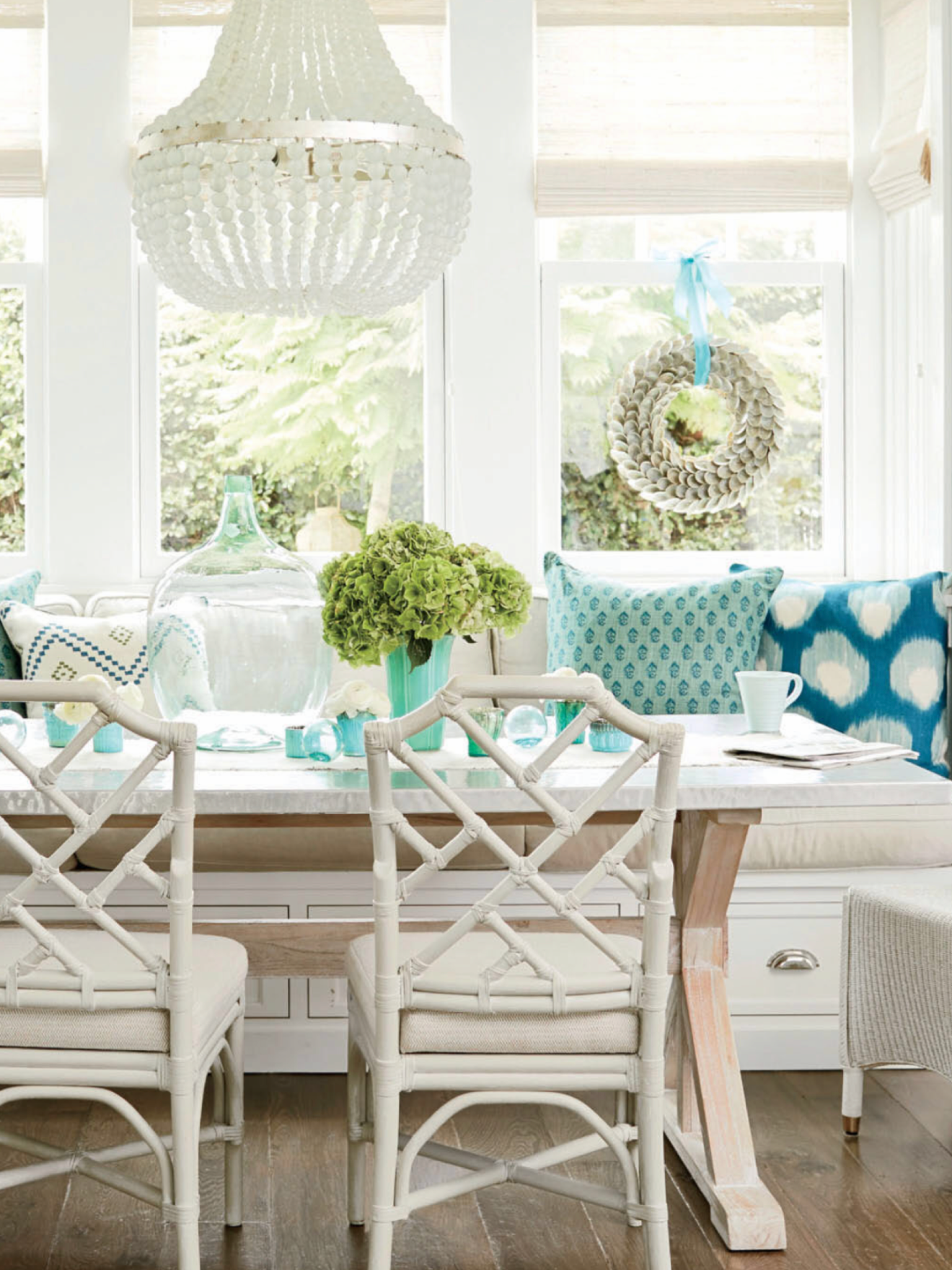 dining nook, wooden floor, white wall, white bench with drawers, blue pillows, white wooden table, white wooden chairs, chandelier, white chair