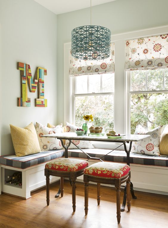 dining nook, wooden floor, white wall, white corner bench, plaid cushion, blue pendant, wooden table, red stools
