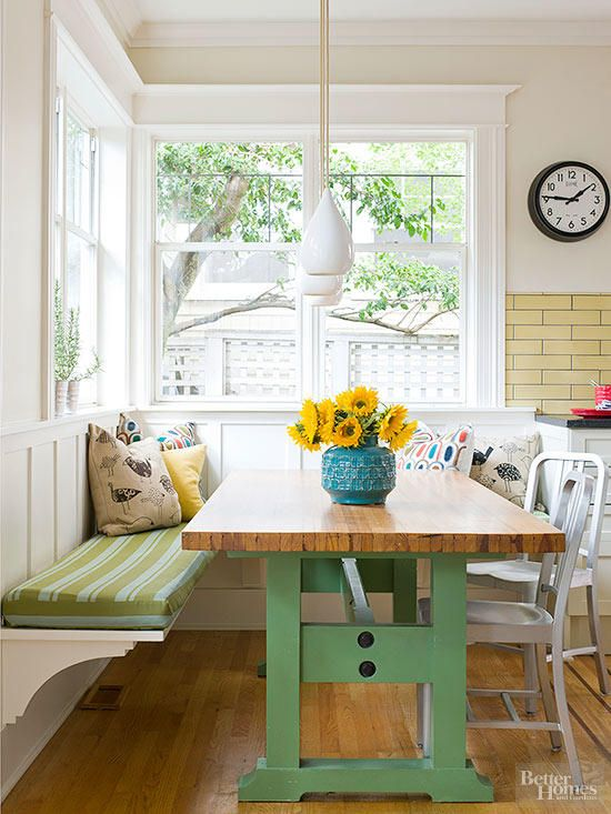 dining nook, wooden floor, white wall, yellow subway tiles, green wooden table, white bench, green cushion, white chairs