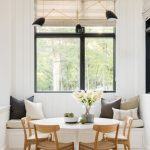 Dining Nook, Wooden Floor, White Wooden Vertical Wall, White Round Table, Wooden Chairs, White Bench With White Cushion, Black Pendant