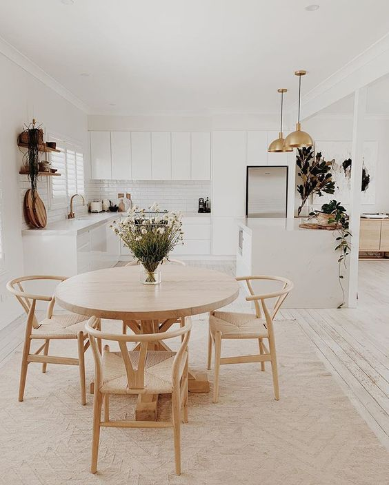 dining room, wooden round table, wooden rattan chairs, patterned floor tiles, white kitchen