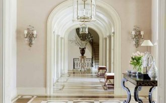entrance, brown patterned floor, pale brown wall, glass chandeliers, scoves, black console table, archs