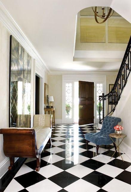 entrance foyer, white wall, black white checkered floor tiles, wooden bench with white cushion, blue chair, golden side table