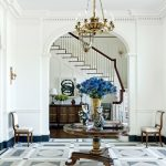 Foyer, Patterned Floor, White Wall, Golden Chandelier, Wooden Round Table, Wooden Chair With White Cushion, Wooden Floor, Dark Blue Lines At The Bottom Of The Wall