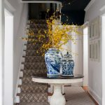 Foyer, White Wall, Dark Blue Ceiling, Crystal Chandelier, White Wooden Roun Table With Black Top, Wooden Floor, Rug