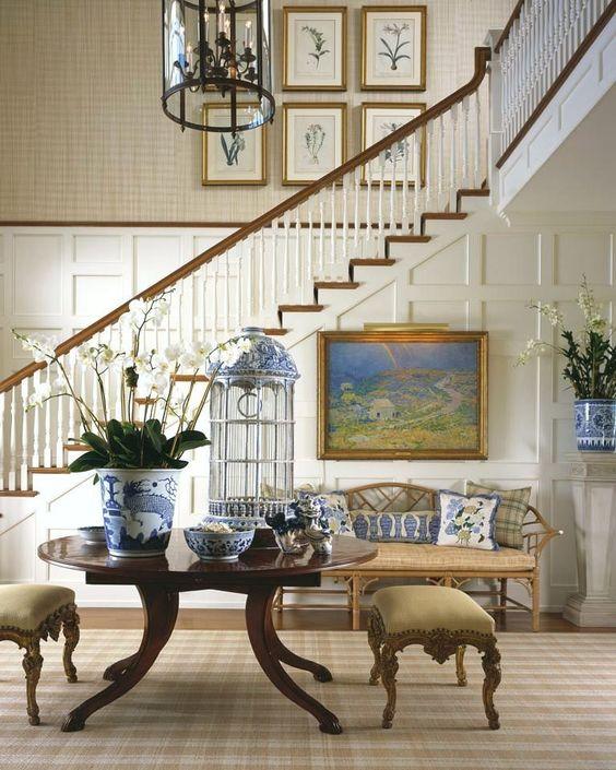 foyer, wooden floor, brown rug, dark brown wooden table, brown ottomans, white wooden wall, rattan bench, brown wallpaper, black metal round pendant