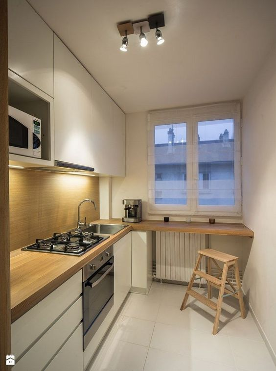 galley kitchen, white floor, white wall, wooden cabinet top, wooden built in table, wooden stair and tool, white cabinet, window