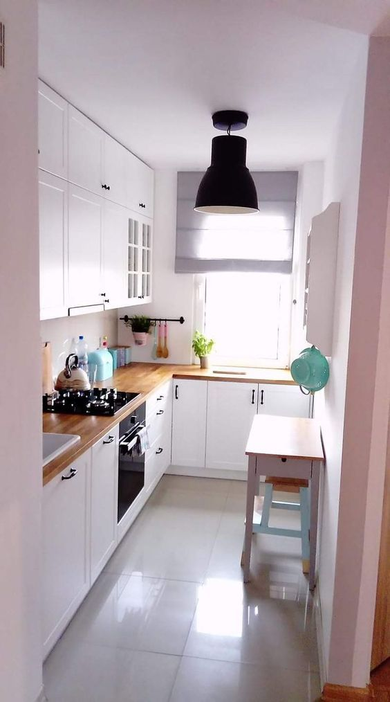 galley kitchen, white wall, white floor, white cabinet with wooden top, white table, black pendant
