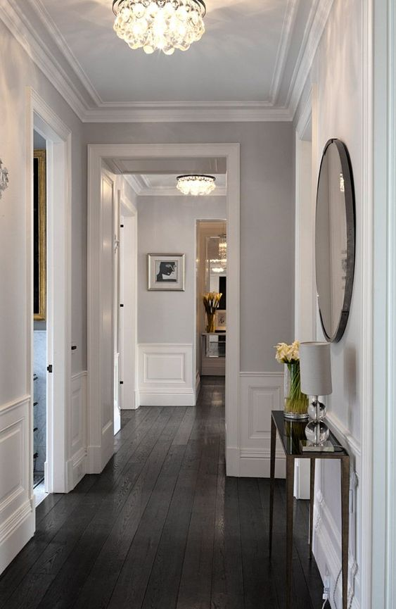 hallway, black wooden floor, white wainscoting, light grey wall, crystal ceiling lamp, slim console table, round mirror
