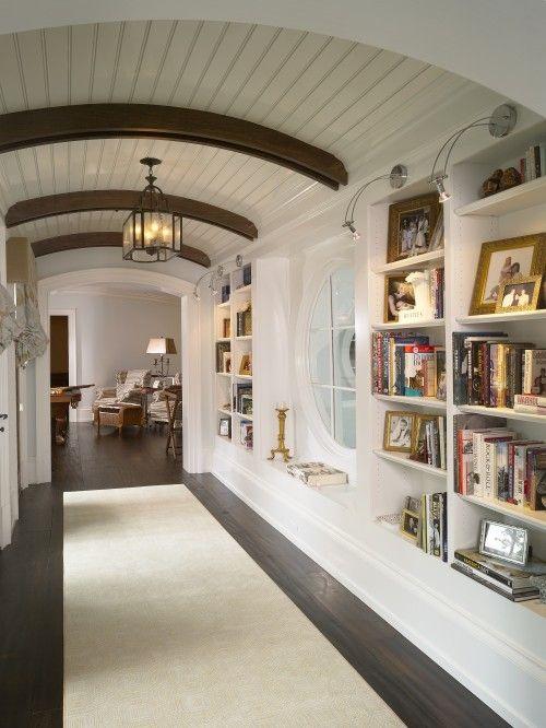 hallway, white built in bokshelves, dark wooden floor, white long rug, white wooden ceiling, wooden beams, chandelier