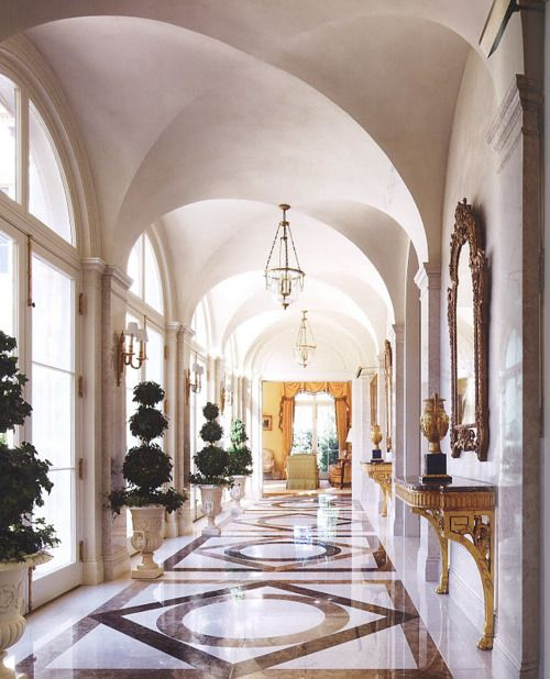 hallway, white marble wall, large glass window and doors, patterned marble floor, chandelier, golden console table, golden framed mirror
