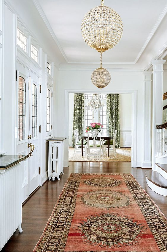 hallway, white wall, white ceiling, crystal globe chandelier, wooden floor, rug pattern rug